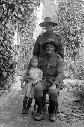 Australian troops pose with a small girl