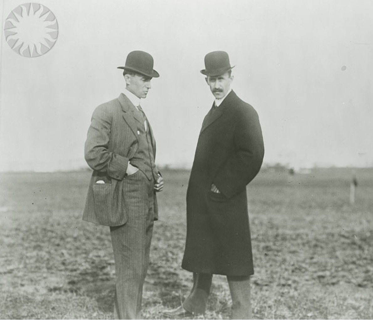 SI Neg. 2002-23708. Date: na...Full length view of the Wright brothers standing in a field; Wilbur is at left, Orville at right, wearing overcoat. Both are wearing derby type hats. Photo taken either January or April 1909 in either Rome, Italy, or Pau, France, during their European tour...Credit: Unknown. (Smithsonian Institution)